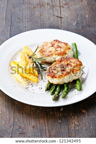 Fishcakes with french fries and asparagus