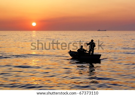 Fisher boat on sunset - stock photo