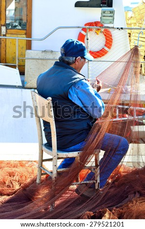fisher clinches the fishing net - stock photo