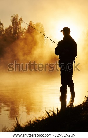 Fisher man fishing with spinning rod on a river bank at misty foggy sunrise - stock photo