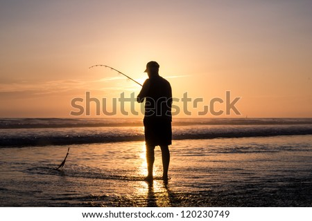 Fisher man with fishing rod on the beach at sunset - stock photo