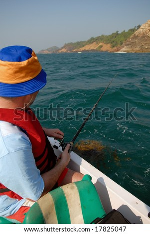fisher on boat - stock photo