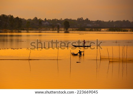 Fisher on boat in water season in sunrise in Dong Thap, Vietnam - stock photo