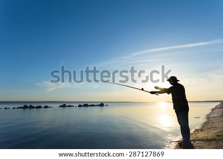 fisher silhouette on a river - stock photo