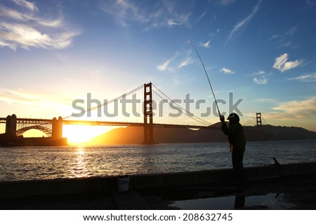 Fisherman and Golden Gate Bridge silhouette during sunset - stock photo