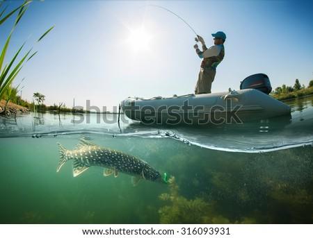 Fisherman and pike, underwater view  - stock photo