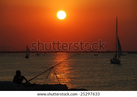 Fisherman and yacht silhouettes on sunset - stock photo