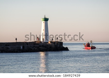 Fisherman at dawn around the lighthouse, in the embouchure of the Herault river,  Agde, France - stock photo