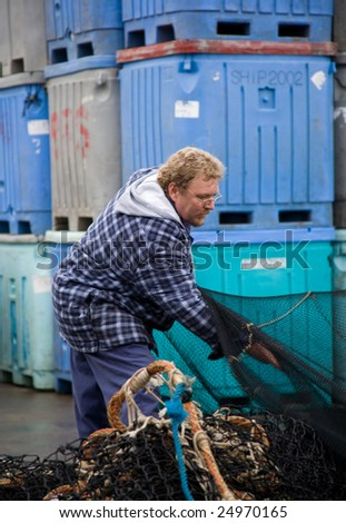 Fisherman at work, preparing fish nets - stock photo