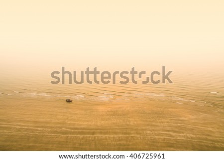 fisherman boat at beach during morning fog - stock photo