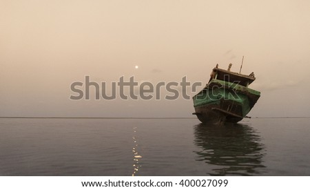 Fisherman boat resting on the shore at dawn - stock photo