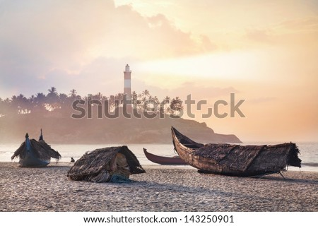 Fisherman boats on the beach in the morning at lighthouse background in Kovalam, Kerala, India - stock photo