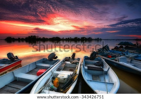 Fisherman bots parked during sunset with nice reflection of sky. Soft focus due to long exposure shot. Vibrant colors. - stock photo