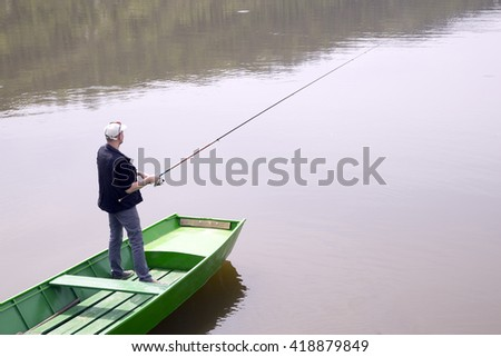 Fisherman Casting A Fishing Rod From The Green Boat On The Lake And Patiently Waiting For Fish To Take A Bait, Water Reflection - stock photo