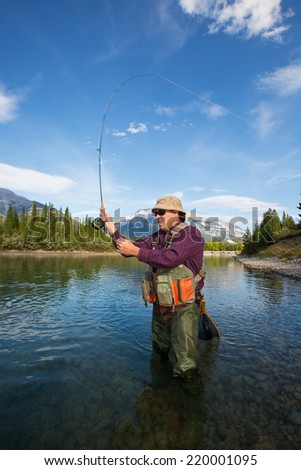 fisherman casting a fly in a mountain river. - stock photo