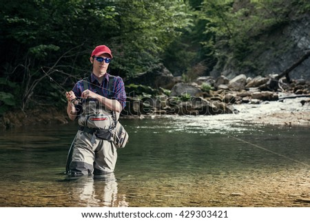 Fisherman catches a fish in the river with fly fishing. Catching trout and bass in the stream. Healthy lifestyle.