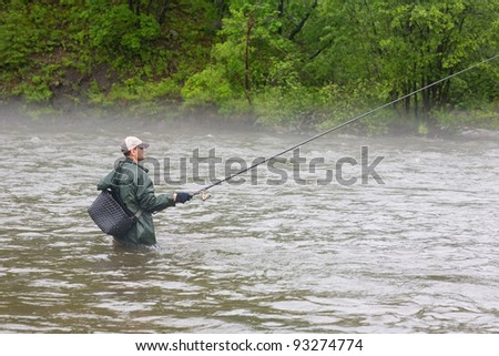 Fisherman catches a salmon river. Fog. Is rain.