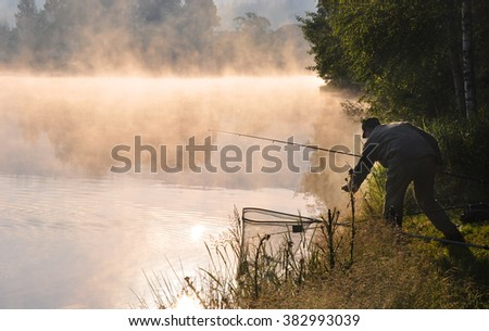 Fisherman catches fish at the small pond in the beautiful morning, South Bohemia, Czech Republic - stock photo