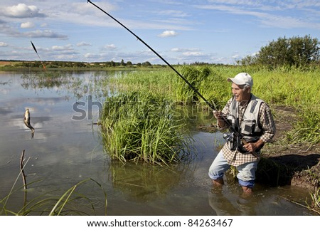 Fisherman catches of carp on the river - stock photo