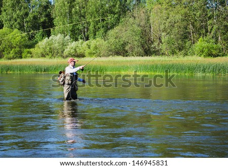 Fisherman catches of chub  fly fishing in the Chusovaya river in the afternoon