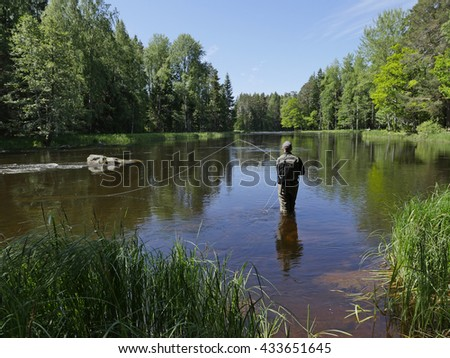 Fisherman catches of salmon fly fishing in the river at summer - stock photo