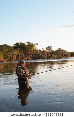 Fisherman catches of salmon in the sunset. Autumn. - stock photo