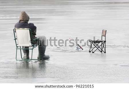 Fisherman catching a fish on a frozen lake in winter. - stock photo
