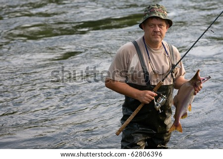 Fisherman caught a salmon (pink salmon) on the River. Early Morning. - stock photo
