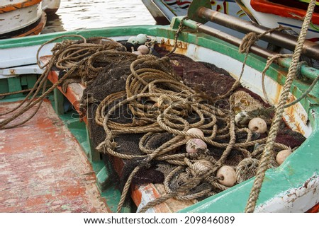 Fisherman complected net on small wooden boat  - stock photo