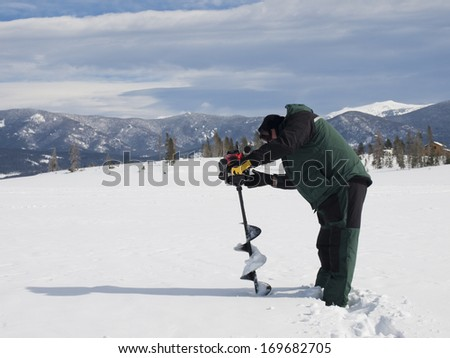 Fisherman eith an auger on the frozen lake Granby, Colorado.
