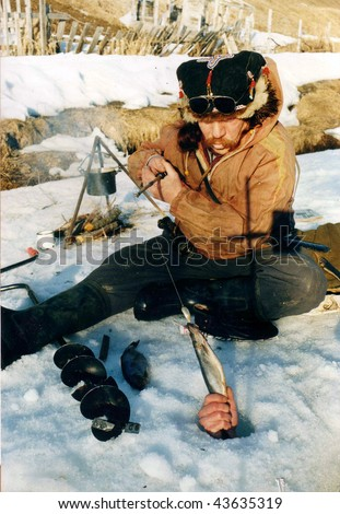 Fisherman enjoying a day on the ice on a bright sunny day - stock photo