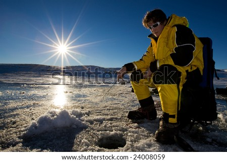 Fisherman enjoying a day on the ice with a low setting sun - stock photo