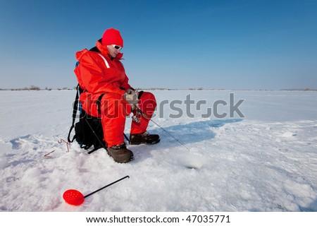 Fisherman enjoying a days fishing on the ice - stock photo