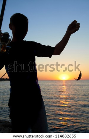 Fisherman fishes on the lake. Silhouette at sunset - stock photo