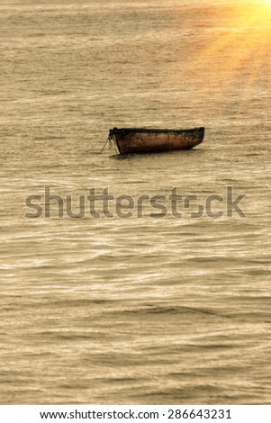 fisherman fishing boat moored at anchor in an open sea - stock photo