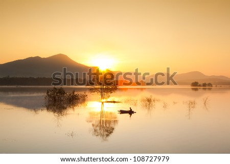 fisherman fishing in big lake ,thailand - stock photo