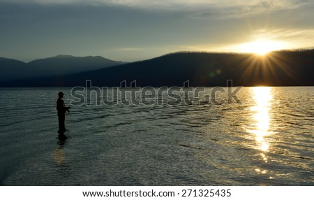 fisherman fishing in McDonald lake in Glacier National Park, Montana at sunset in summer