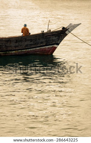 fisherman fishing off a moored dhow boat at anchor against a calm water background - stock photo