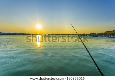fisherman fishing rod in ocean at dawn with colorful sky and water reflection. wide angle view