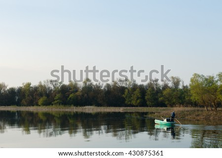 Fisherman floating on a boat on the river on a summer day - stock photo