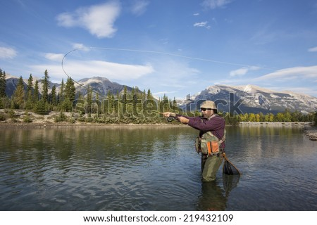 fisherman fly fishing in a mountain river. - stock photo