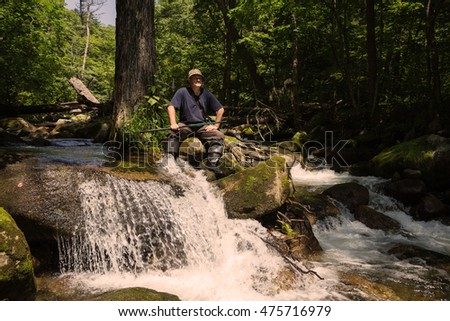 Fisherman has a rest sitting on a rock by the river