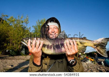 fisherman holding a big fresh caught fish - stock photo