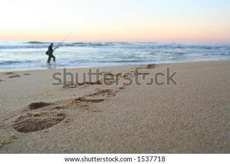 Fisherman in a beach sunset - stock photo