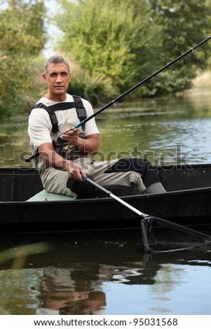 Fisherman in a boat - stock photo