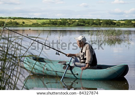 Fisherman in a boat during the sunny day - stock photo