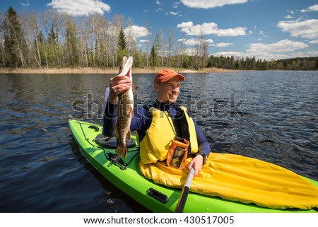 Fisherman in a kayak holding a caught fish (northern pike)  - stock photo