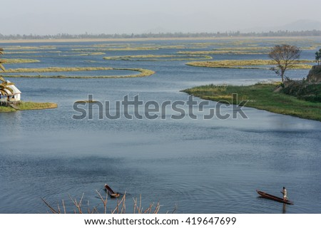 Fisherman in boat at Loktak Lake, the largest freshwater lake in North-East India, famous for phumdis or Keibul Lamjao, world's only floating national park in Manipur, India  - stock photo