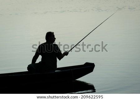 Fisherman in Boat on a Twilight Lake - stock photo