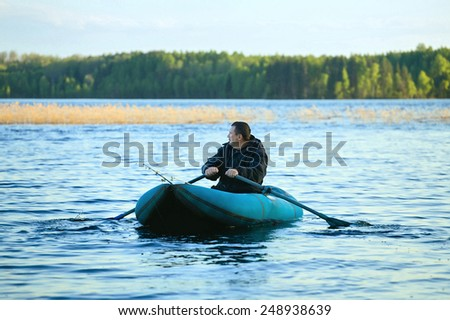 fisherman in rubber boat on a lake - stock photo